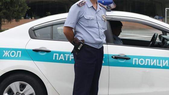 Полицейский стоит у служебного авто