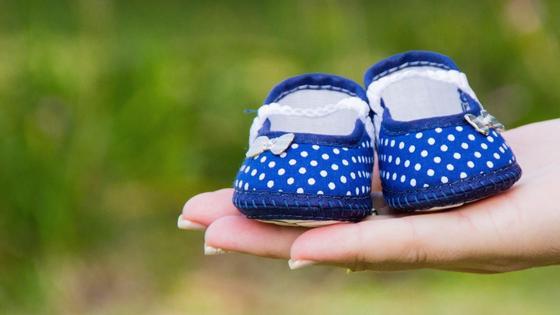 Женщина держит в руках детские ботинки