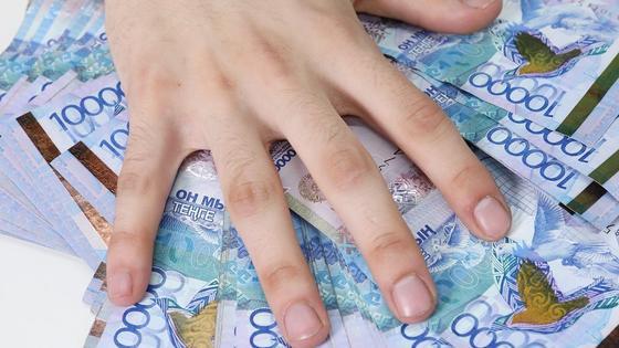 Рука лежит на 10-тысячных купюрах тенге