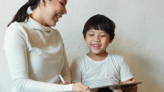 Женщина с ребенком держат в руках планшет