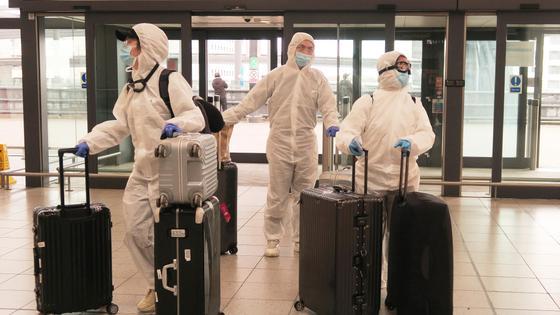 Врачи в защитных костюмах в аэропорту