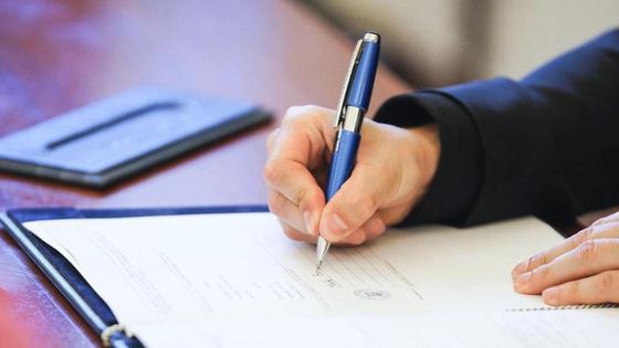 Женщина проводит ручкой по бумаге