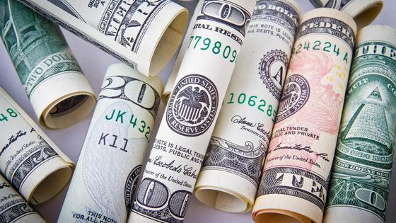 Долларовые купюры лежат скрученные в трубочку