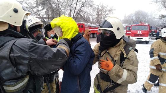 Пожарные стоят вокруг мужчины на фоне спецтехники