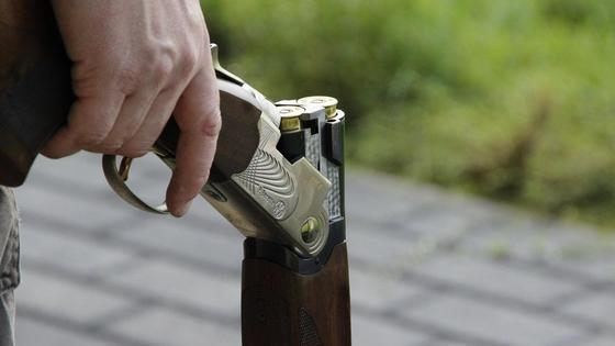 мужчина держит ружье в руке