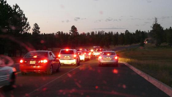 Автомобили с включенными фарами едут по дороге