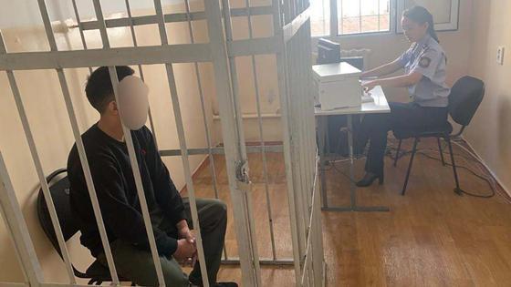 Мужчина сидит в клетке в одной комнате с полицейским