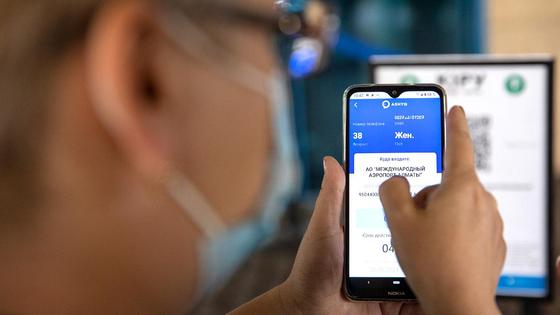 Женщина держит в руках смартфон с открытым приложением Ashyq