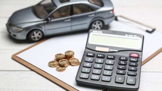 Калькулятор, монеты и модель машины на планшете