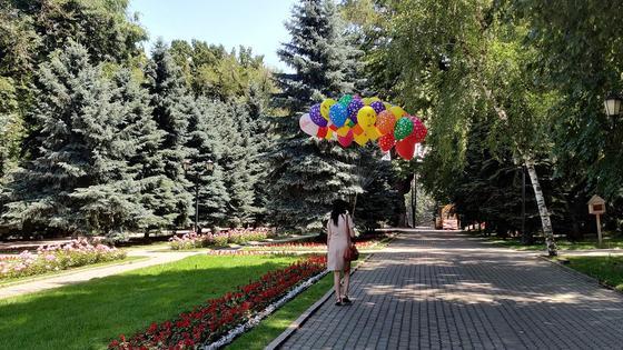 Девушка с шарами идет по парку
