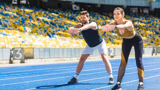 Мужчина и женщина занимаются спортом на стадионе