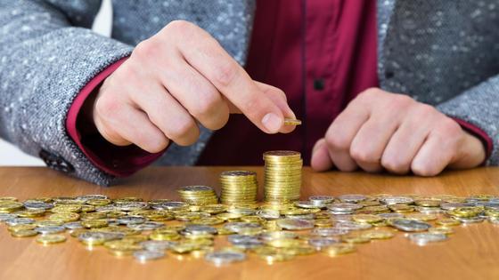 Мужчина собирает монеты тенге в стопки