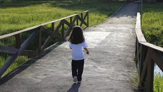 девочка Кира идет по мосту