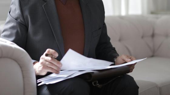Мужчина сидит на диване и смотрит бумаги
