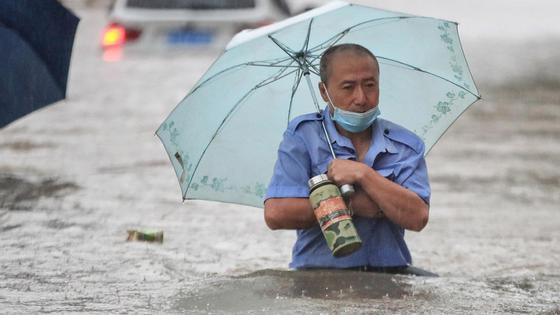 Мужчина под зонтом в воде