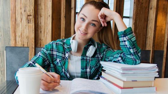 Девушка за столом с книгами и конспектами