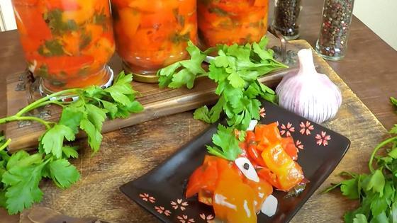 Перевернутые банки с перцем, салат из перца на тарелке, зелень петрушки и чеснок