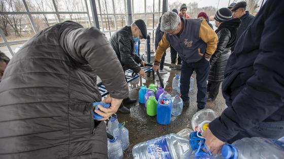 Люди набирают воду возле колонки