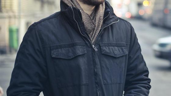 Мужчина в куртке стоит на улице