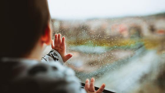 Ребенок стоит у окна