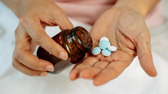 Женщина держит в руках баночку с лекарствами