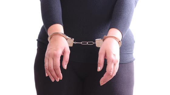 Женщина стоит в наручниках