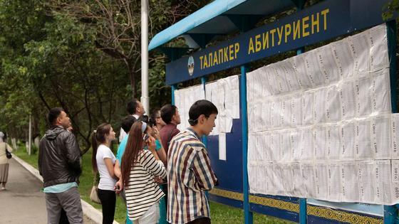 Казахстанские студенты смотрят на доску объявлений в вузе