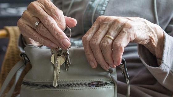 Пожилая женщина держит в руках сумочку и ключи