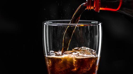Газированный напиток коричневого цвета наливают в бокал