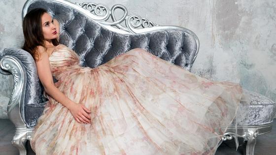 Девушка в вечернем пышном платье на диване