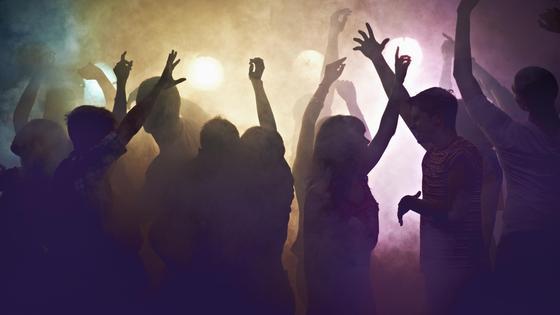 Толпа танцует в дыму в ночном клубе