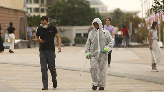 Мужчина в маске идет рядом с дезинфектором