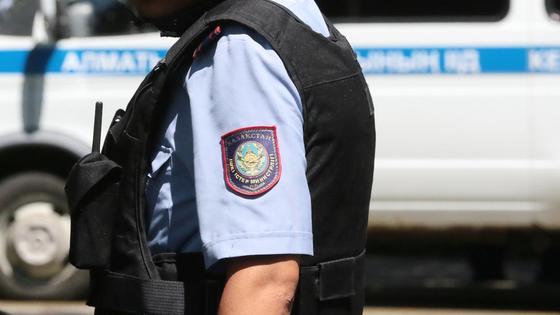 Полицейский в форме стоит возле служебного автомобиля