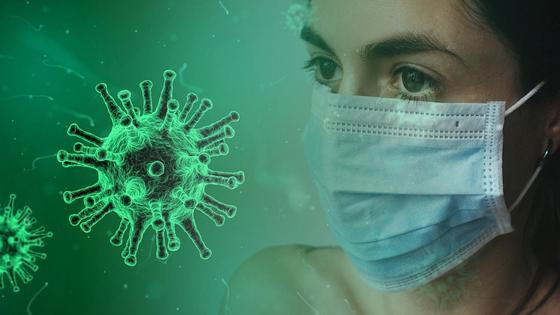 Девушка в маске смотрит на изображение вируса