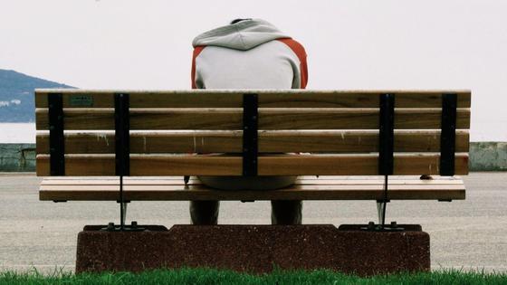 Мужчина сидит на скамейке