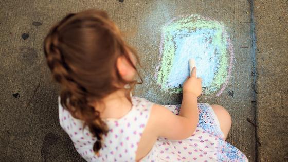 Девочка рисует мелом на асфальте