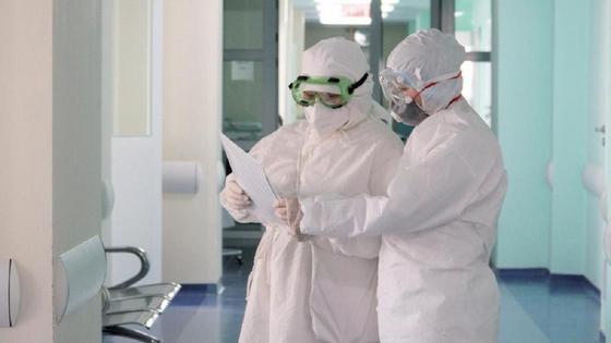 Врачи в СИЗах стоят в коридоре больницы