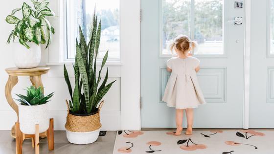 Девочка в белом платье стоит у двери