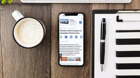Мобильный телефон, чашка кофе и планшет на столе
