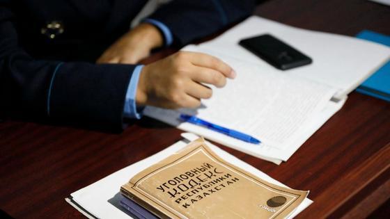 Следователь сложил руки на стол рядом с уголовным кодексом