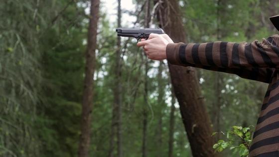 Парень держит пистолет в руках