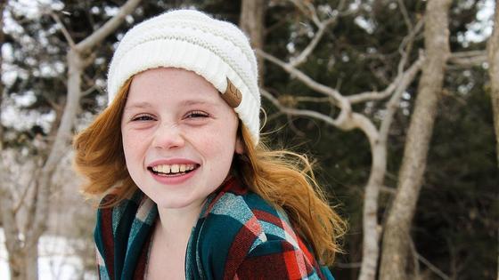 рыжая девочка улыбается