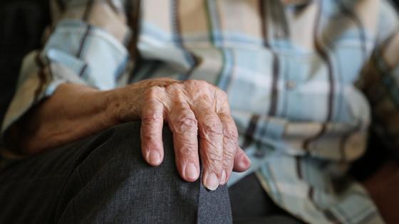 Пожилой мужчина сидит, положив руку на колено