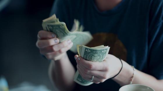 Женщина пересчитывает доллары