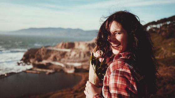 Девушка на берегу моря смеется