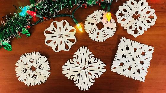 Бумажные снежинки возле елочной етки с гирляндами
