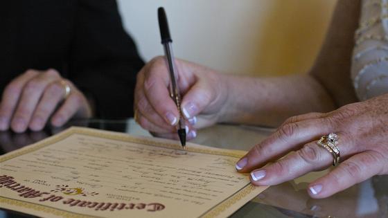 Женщина подписывает свидетельство о браке