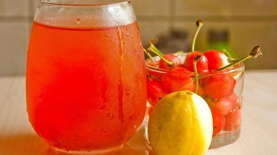 Стакан с вишневым компотом, стакан с вишнями и лежит лимон