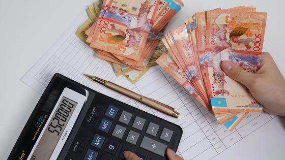 Женщина считает деньги на калькуляторе