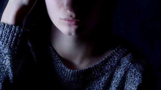 Девушка на темном фоне позирует для камеры